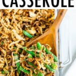 Casserole dish with healthy green bean casserole topped with crispy onions. A wood spoon is scooping some of the casserole.