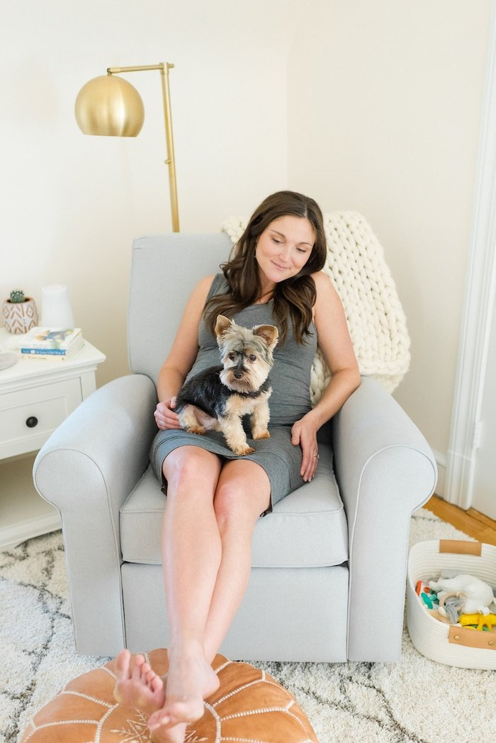 Pregnant woman sitting in glider with dog on lap.