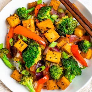 Bowl of rice with tofu and vegetable stir fry on top. Chopsticks are resting on the bowl.