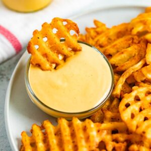Waffle fry being dipped into homemade Chick-Fil-A Sauce.