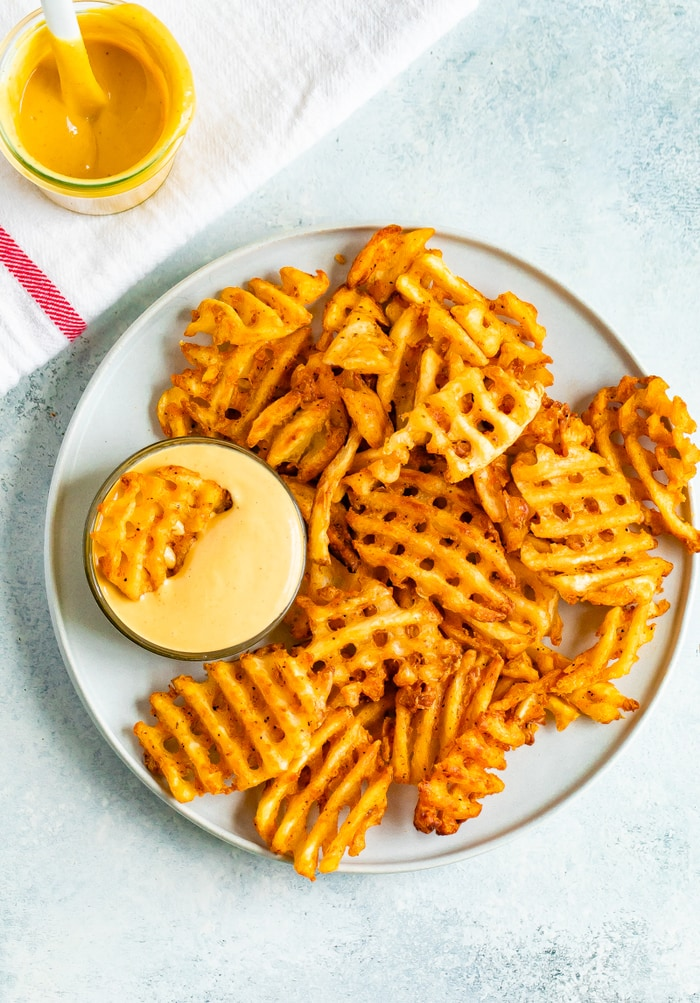 Plate of waffle fries with a bowl of Chick-Fil-A Sauce that one fry is being dipped into.