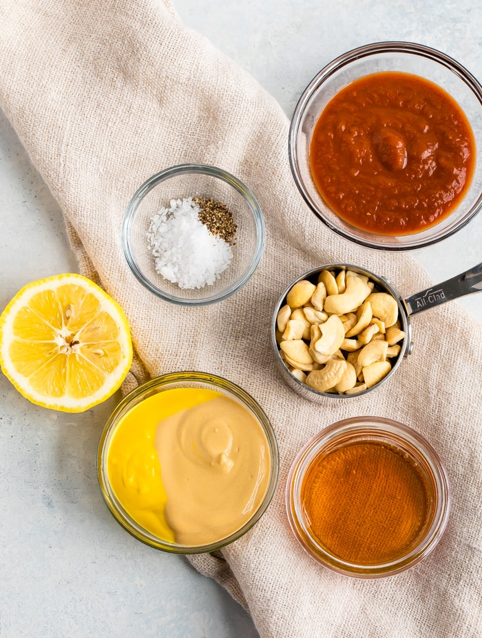 Ingredients to make homemade healthy Chick-Fil-A Sauce in bowls: bbq sauce, salt and pepper, cashews, lemon, mustard, and honey.