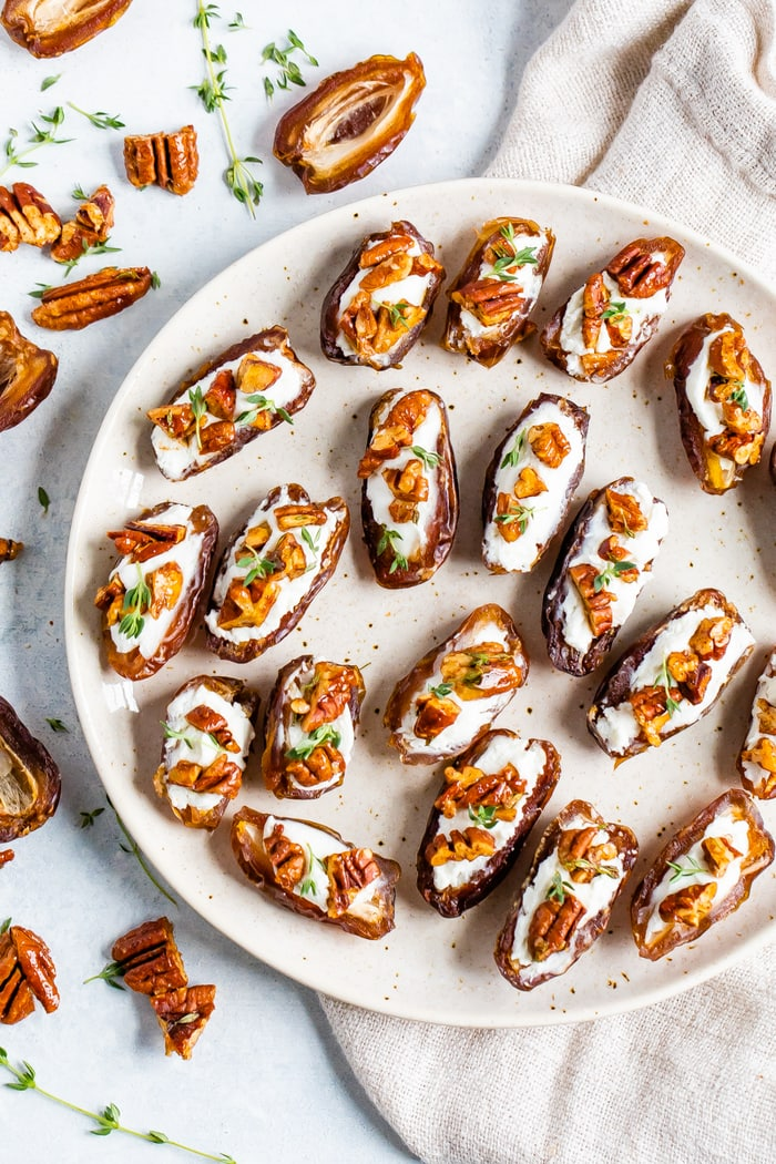 Plate with goat cheese stuffed dates topped with roasted pecans and fresh thyme. Ingredients in this easy recipe are around the plate along with a cloth napkin.