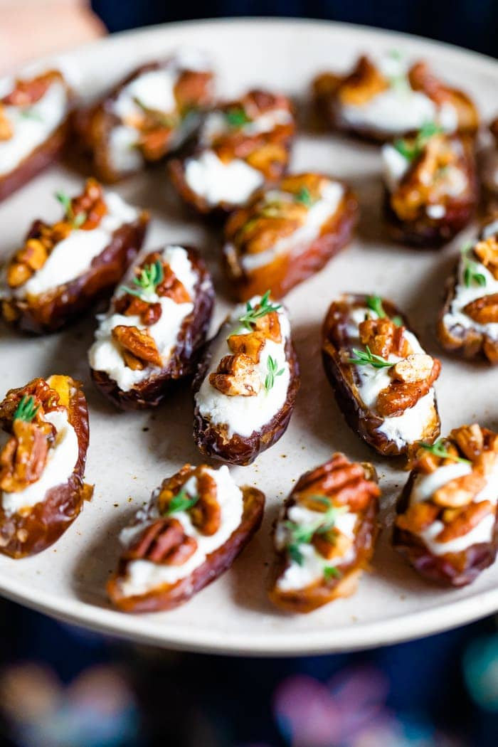 Plate with goat cheese stuffed dates, topped with chopped pecans and fresh thyme.