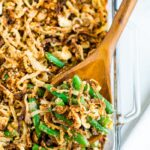 A wooden spoon scooping green bean casserole out of a glass baking dish.