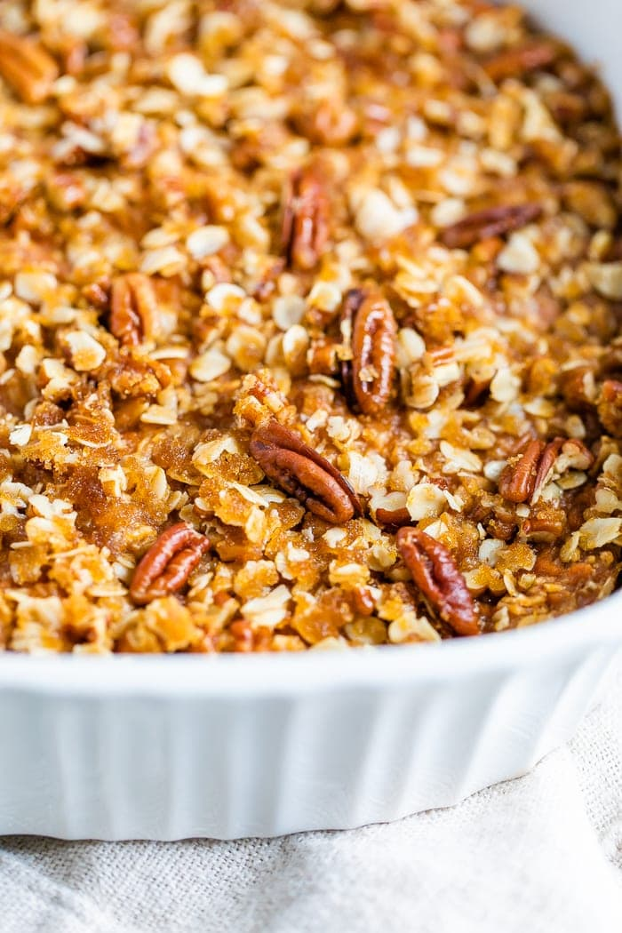 Baking dish with sweet potato baked oatmeal topped with pecans.