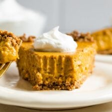 Slice of vegan pumpkin pie topped with whipped cream.