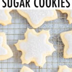 Snowflake and star cut-out cookies on a cooling rack decorated with white icing and sprinkles.
