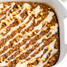 Baking dish with gingerbread baked oatmeal drizzled with frosting.