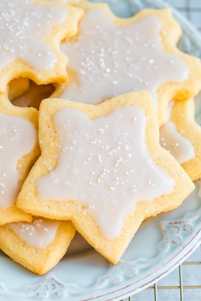 Plate of star and snowflake cut-out cookies with white icing and sprinkles.