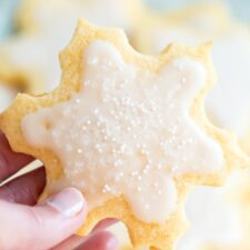 Hand holding a snowflake cut out cookies decorated with white icing and sprinkles.