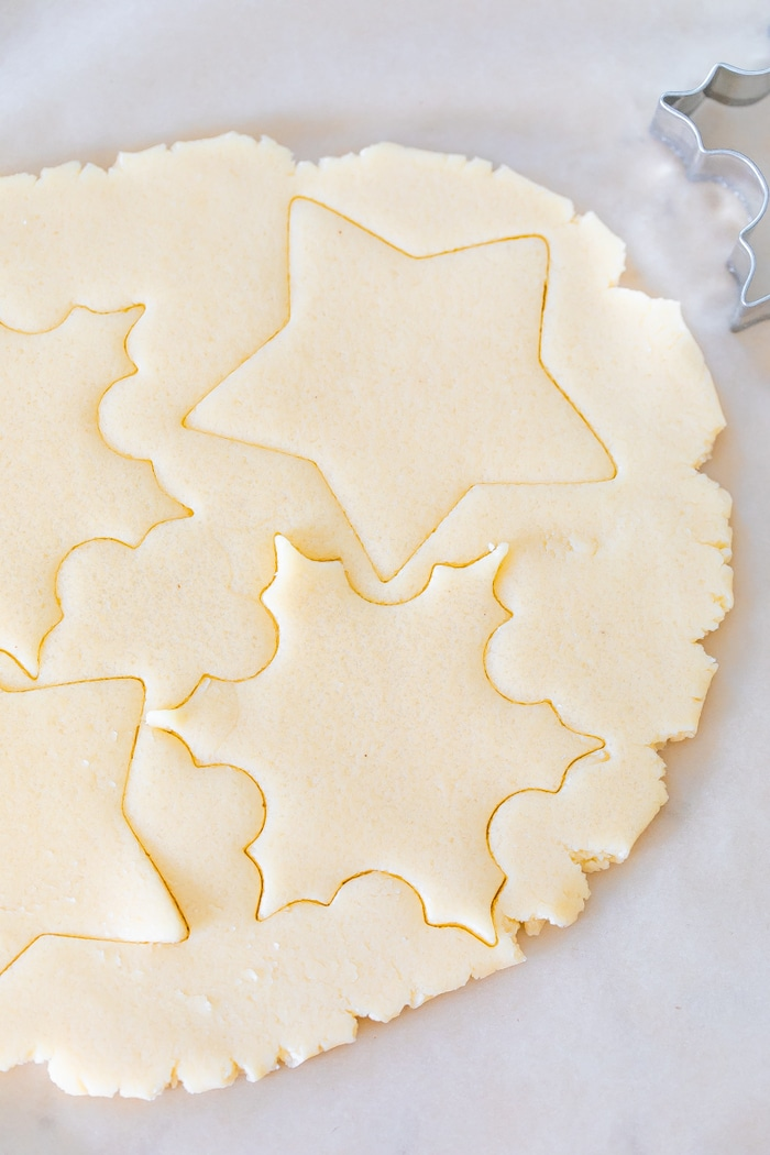 Sugar cookies dough with cut out shapes.
