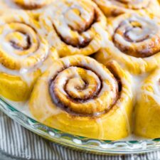 Round baking dish with pumpkin cinnamon rolls drizzled with icing.
