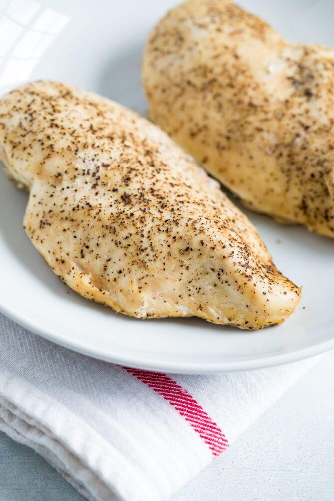 Deux poitrines de poulet cuites à la mijoteuse assaisonnées de sel et de poivre.