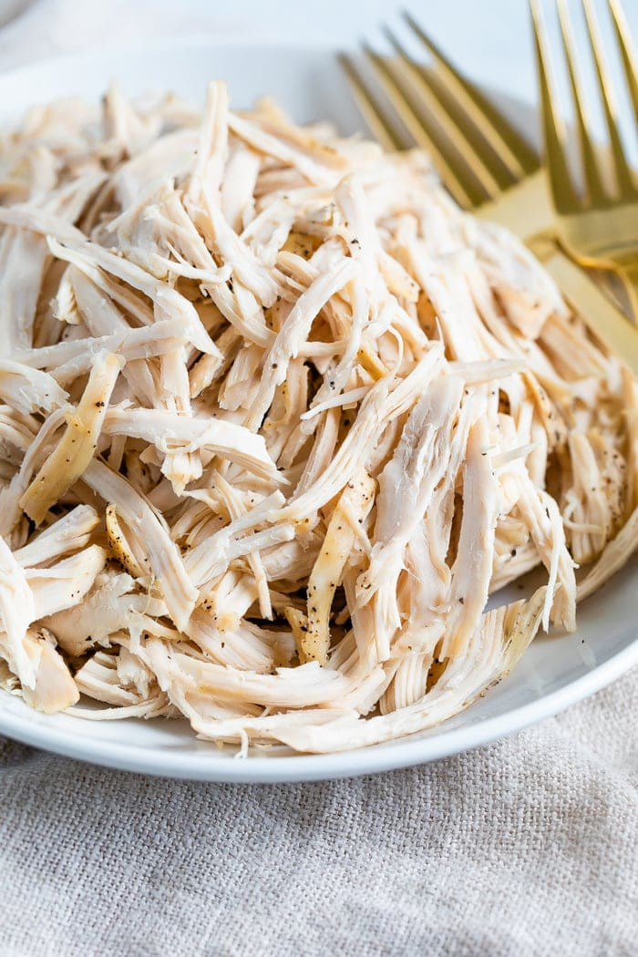 Plate with shredded chicken and two forks.