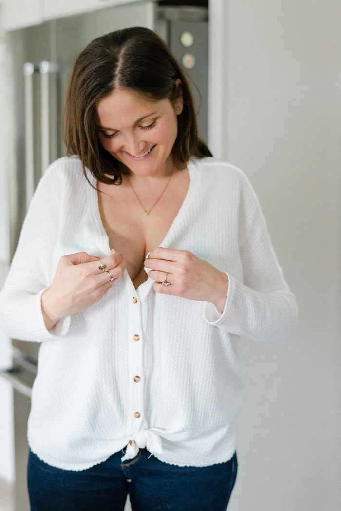 Woman wearing the Willow breast pump and buttoning her white thermal top.
