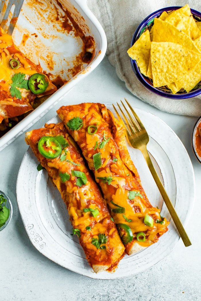 Two chicken enchiladas on a plate.