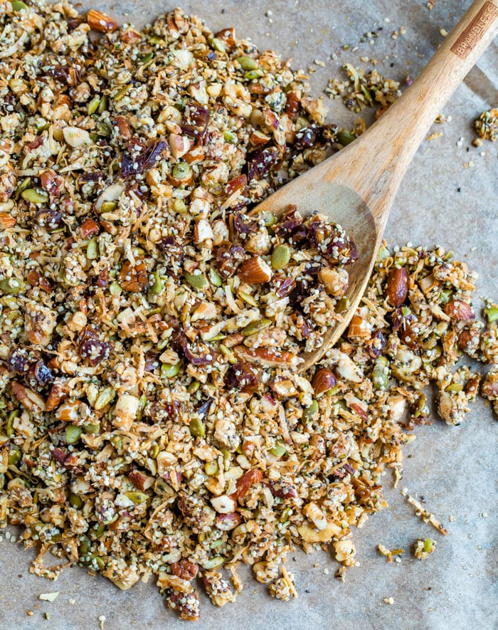 Hemp granola on a baking sheet lined with parchment paper. Wood spoon is on the sheet.