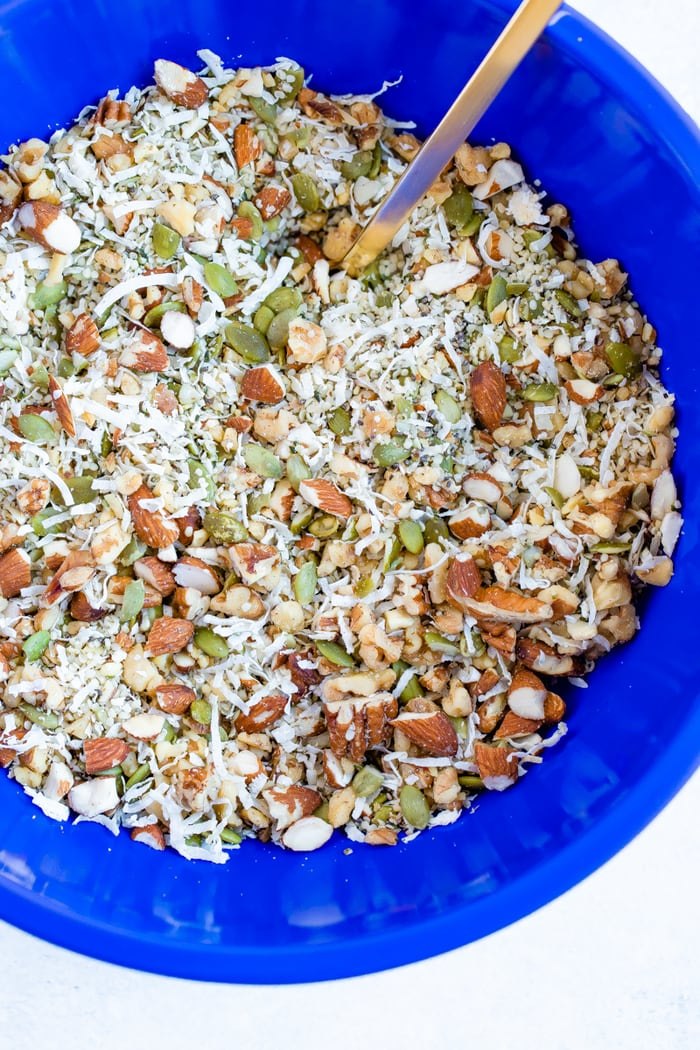 Blue mixing bowl wish ingredients for hemp granola including nuts, seeds and coconut flakes.