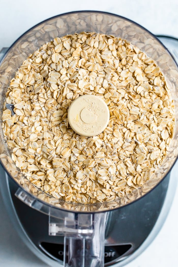 Food processor with rolled oats inside.