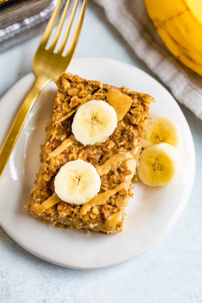 Slice of peanut butter banana baked oatmeal on a plate with a fork and topped with peanut butter drizzle and sliced bananas.