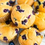 Cluster of blueberry muffins on a gold cooling rack.