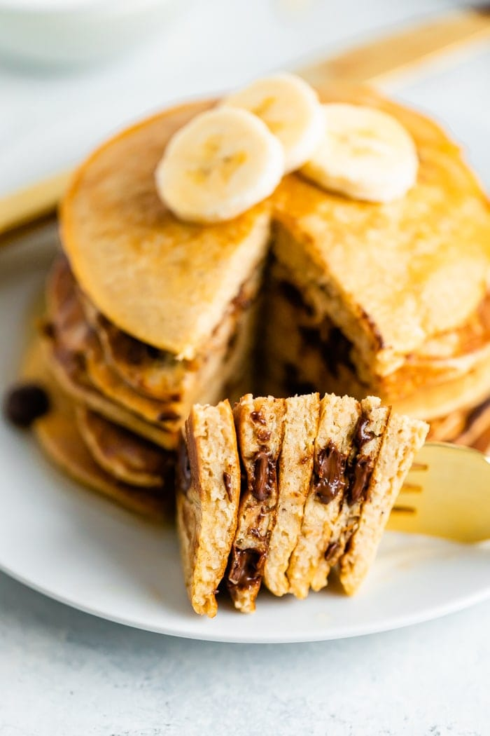 Stack of chocolate chip Greek yogurt pancaked topped with banana slices and with a bite of the stack taken out of it.