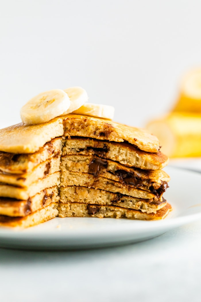 Stack of chocolate chip Greek yogurt pancakes with a slice taken out of the stack.