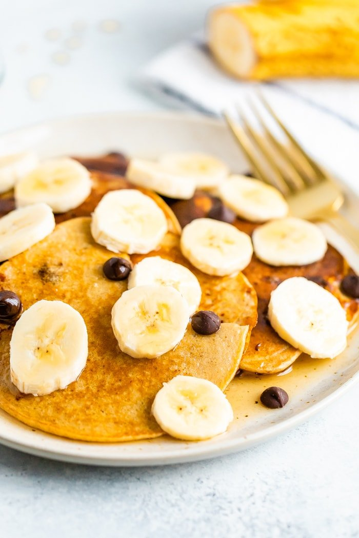 Greek yogurt pancakes on a plate topped with banana slices, chocolate chips and maple syrup.