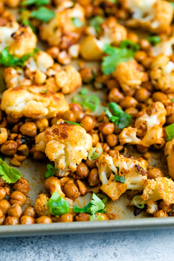 Roasted cauliflower and chickpeas on a sheet pan topped with cilantro.