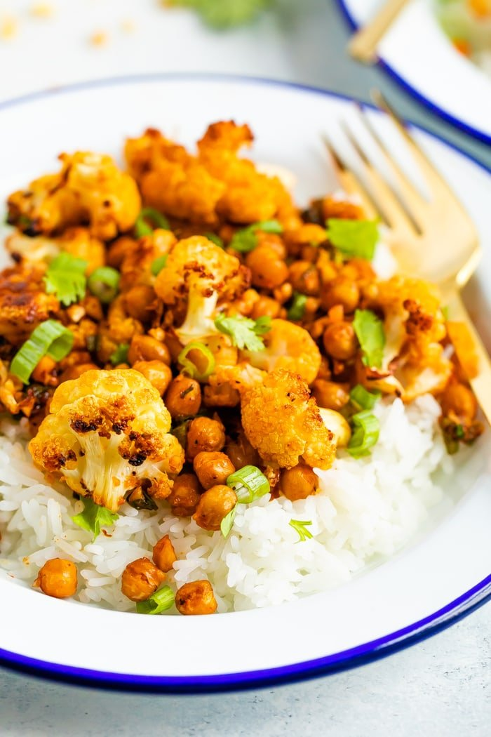 Roasted spicy cauliflower and chickpeas served over rice and topped with cilantro.