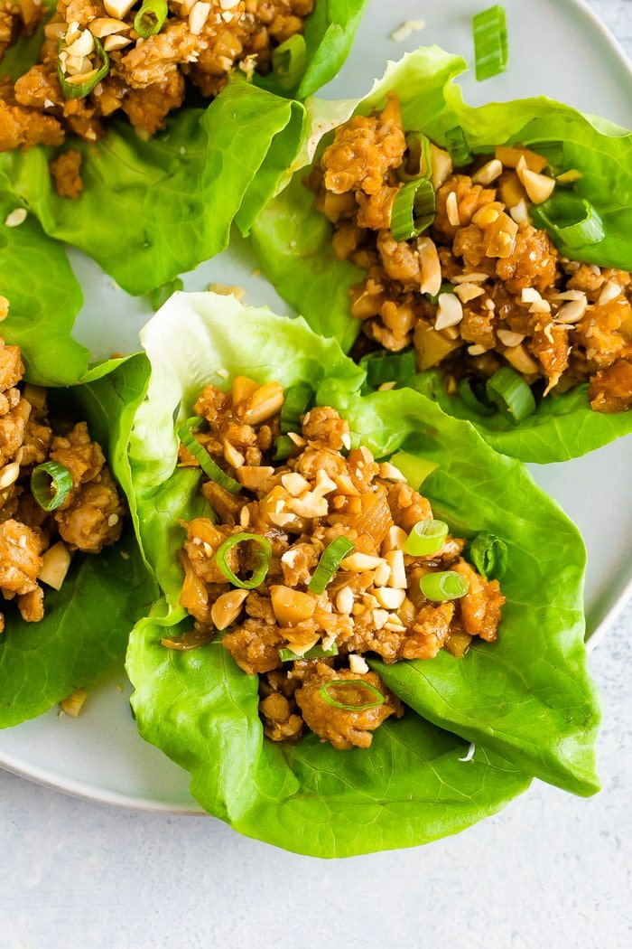 Four chicken lettuce wraps on a plate.