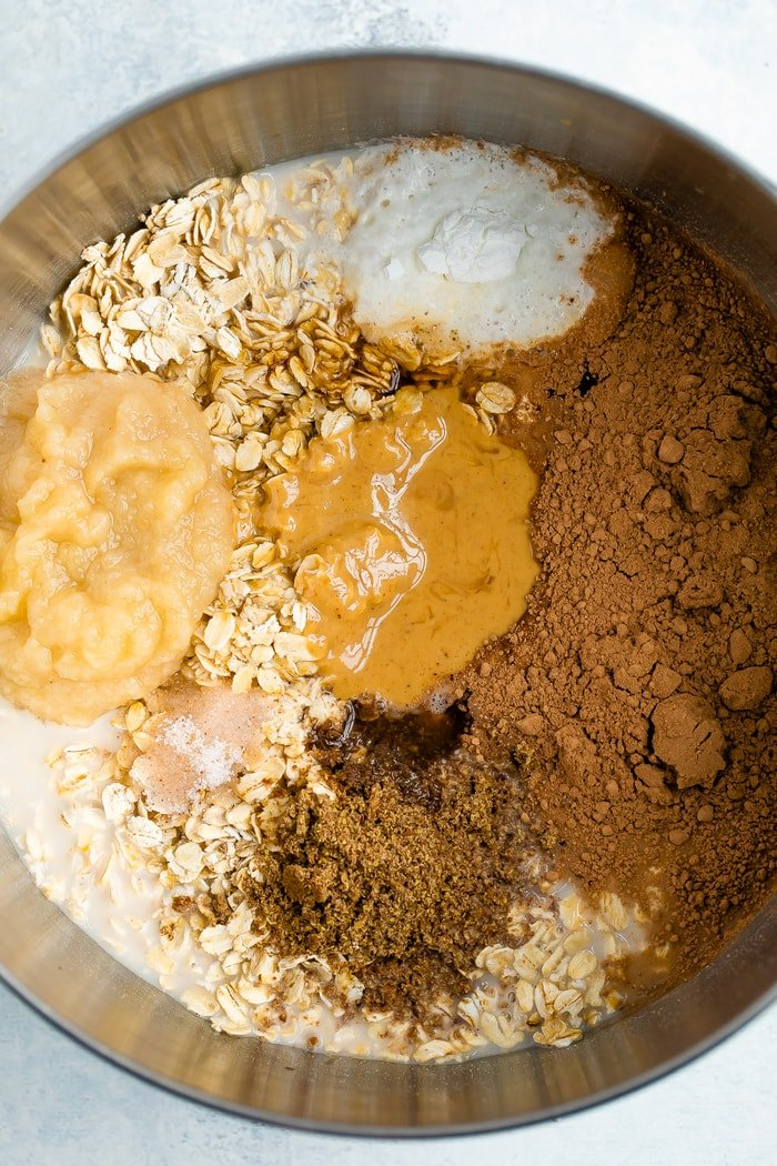 Mixing bowl with ingredients for chocolate peanut butter baked oatmeal.