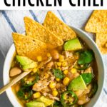 Bowl of white bean chicken chili topped with avocado, jalapeños and corn tortilla chips.