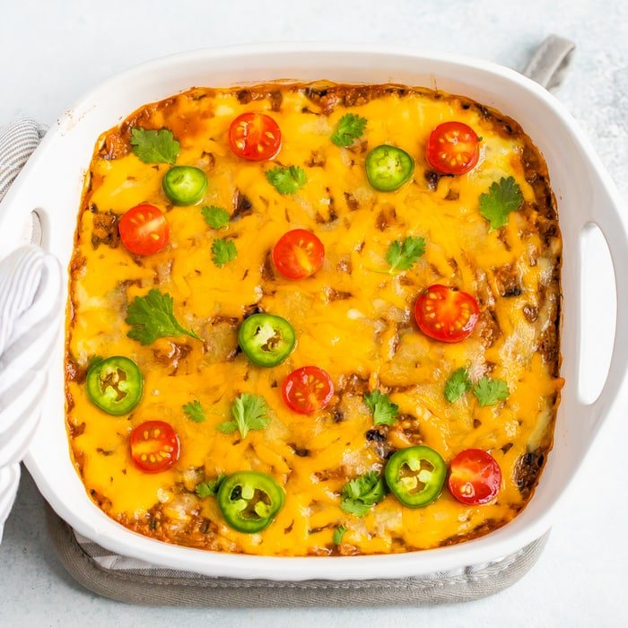 Spaghetti Squash Taco Bake in a casserole dish baked with cheese on top and topped with cilantro, tomatoes and jalapeños.