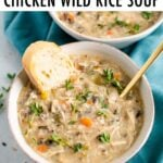 Bowl full of creamy chicken wild rice soup and served with fresh thyme and bread.