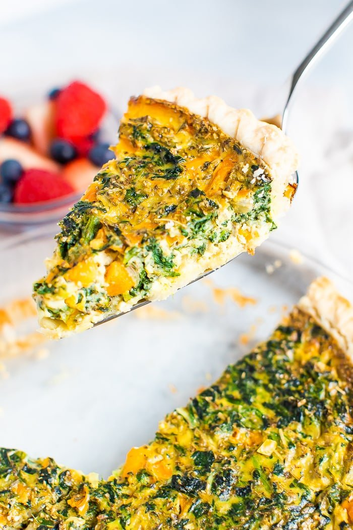 Spatula lifting up a slice of spinach and pepper quiche.