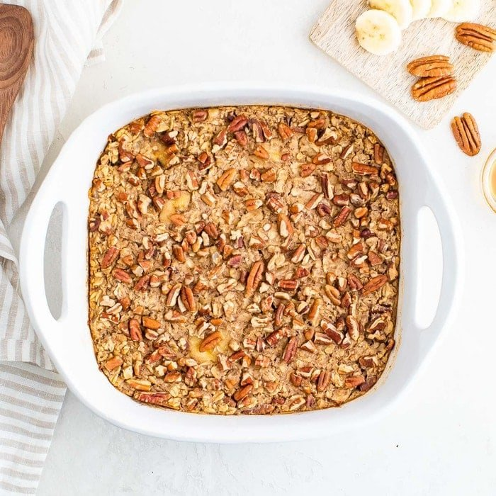 Baked oatmeal in a white baking dish with bananas and pecans.