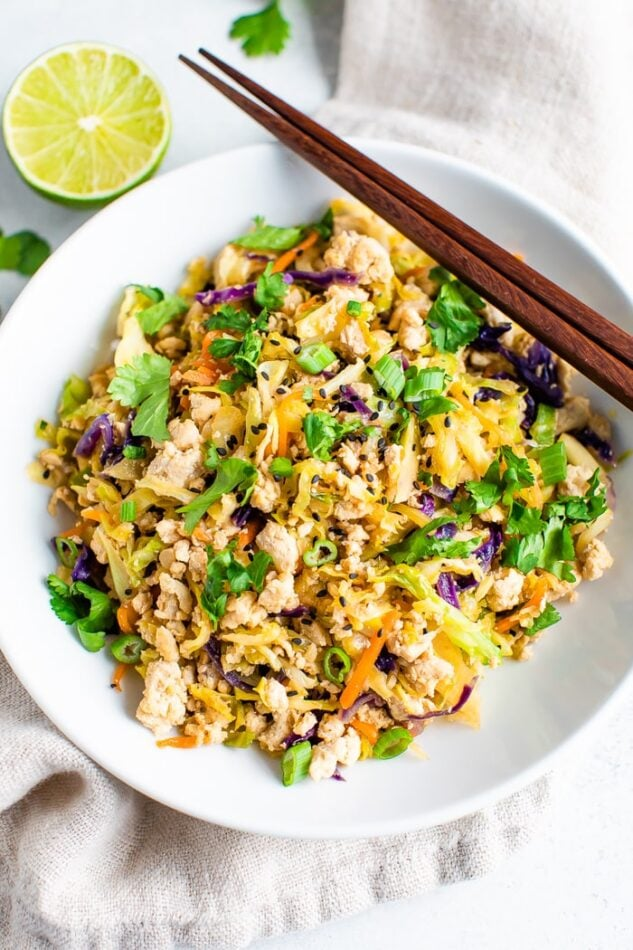 Ground poultry and coleslaw mix together in a bowl with chopsticks and topped with cilantro and lime.