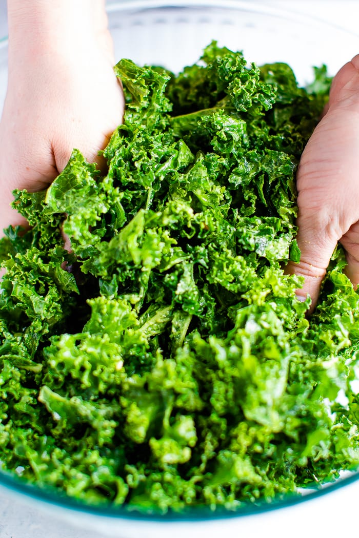 Hands massaging kale salad.