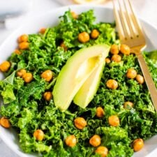 Bowl with kale and topped with lemon and avocado slices and a fork. Lemon halves on the side.