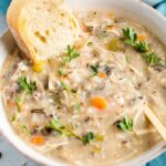 Bowl of wild rice chicken soup served with bread and fresh thyme.