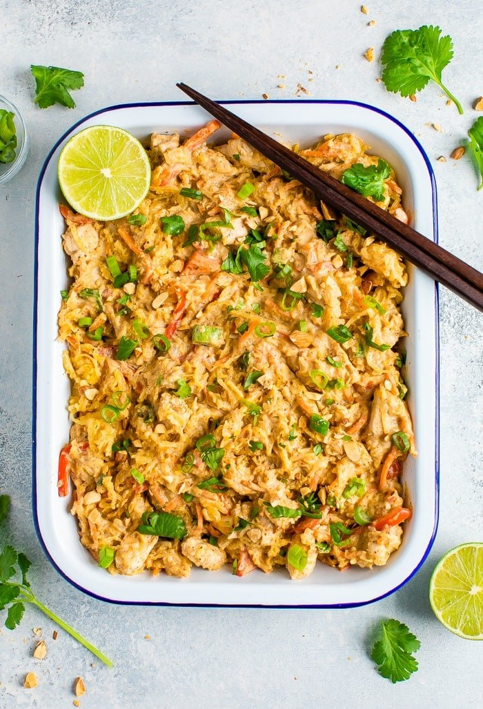 Rectangle serving tray full of spaghetti squash pad thai and topped with cilantro, peanuts, green onions and lime. Chop sticks are resting on the edge of the tray.