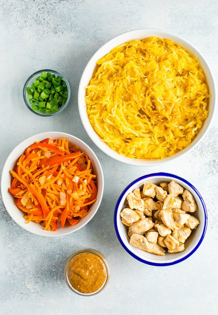 Ingredients to make spaghetti squash pad thai in bowls: green onions, spaghetti squash, carrots and peppers, chicken and almond butter.