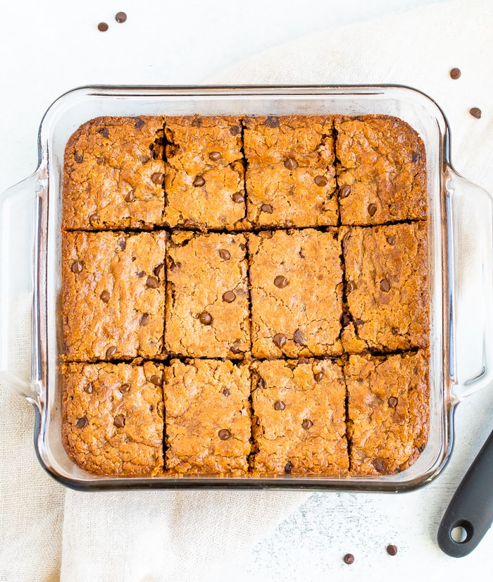 Glass square baking dish with chocolate chip blondies cup into squares.