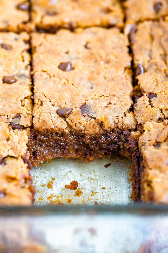 Gooey blondies in a pan cut into squares. One square is already taken.