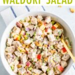 Creamy chicken waldorf salad in a bowl made with apples, celery, onions and walnuts.