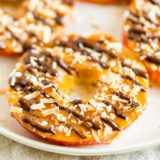 Apple samoas on a plate. Apple rings topped with caramel, chocolate drizzle and coconut flakes.