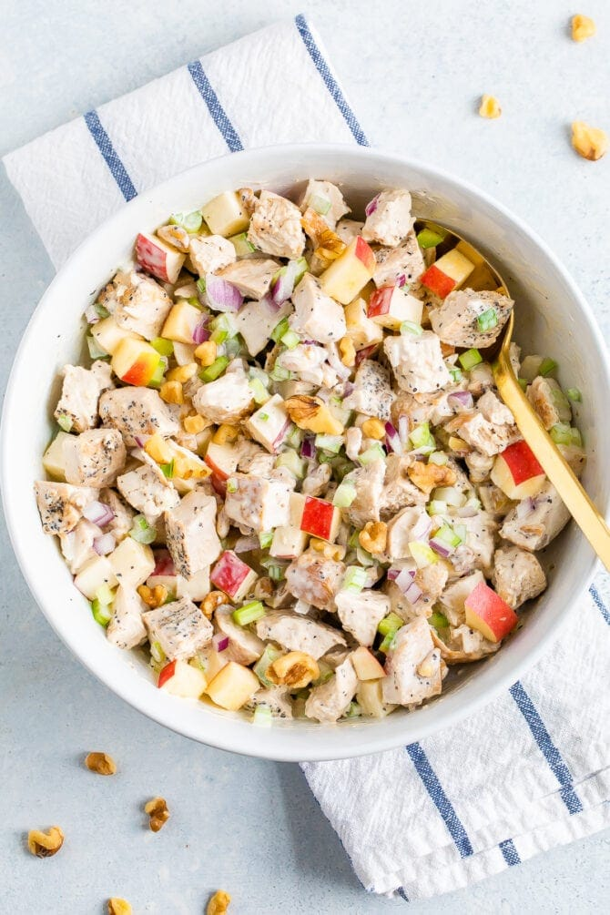 Bowl of chicken waldorf salad made with chunks of grilled chicken, chopped apple, celery, onion, herbs, walnuts and a creamy dressing.