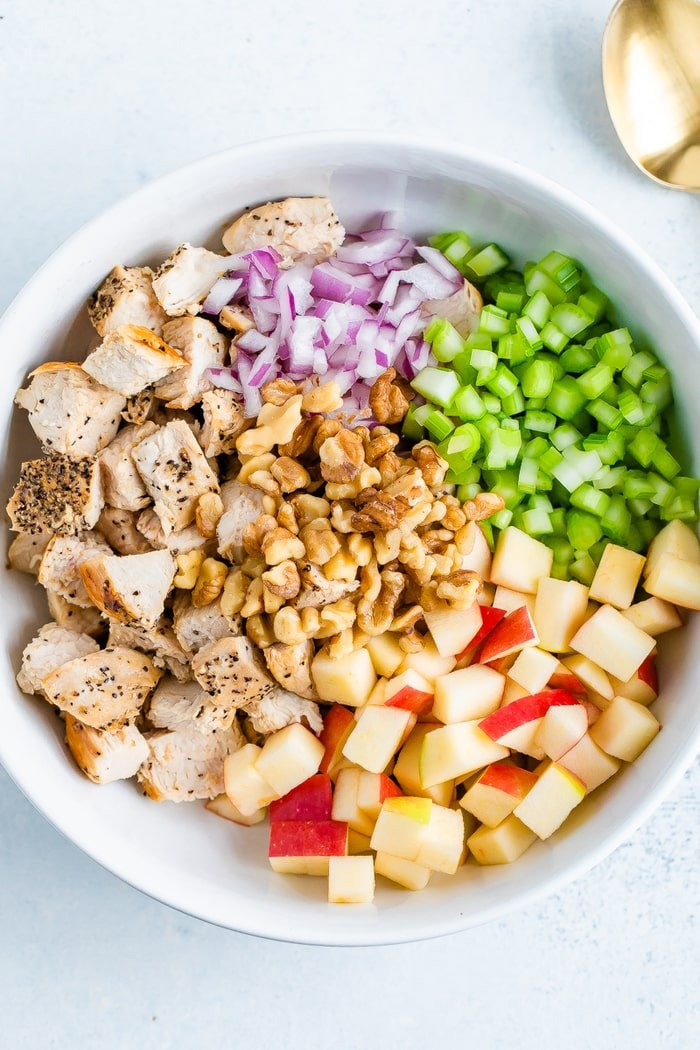 Bowl with the ingredients for a chicken waldorf salad before being mixed-- chopped grilled chicken, red onion, celery, walnuts and apples.